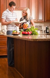 Young couple read through a recipe book in the kitchen with a counter full of fresh vegetables.