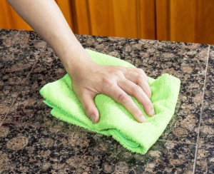 Hand with microfiber cleaning rag wiping stone countertop in kitchen