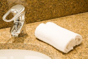 Closeup of a luxurious bathroom sink with fluffy face towels on a granite counter